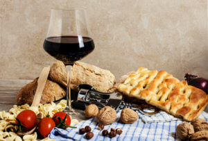 italian food and red wine glass with corkscrew